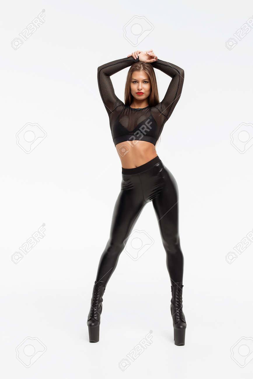 0248a69fbf6 Alluring woman wearing high heels with black leather pants bending..