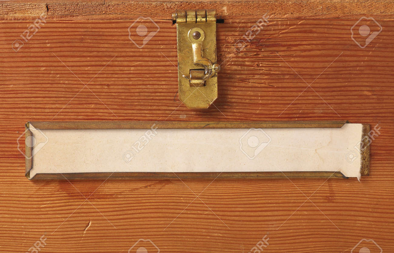 Close up of the front of a simple wooden box featuring a brass latch and label holder with a blank, yellowing label ready for your text. Stock Photo - 8753772