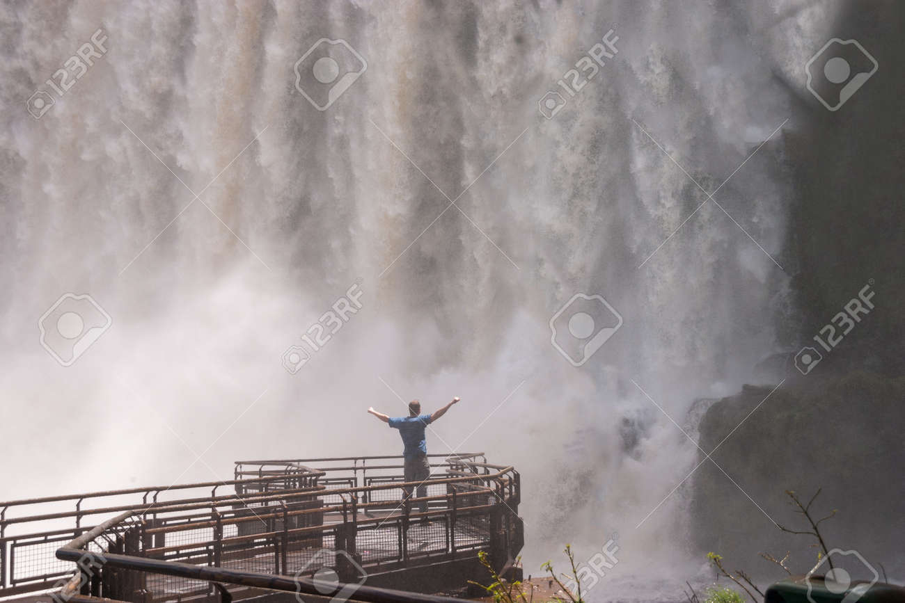 Man standing close to the Iguacu Falls hands up Power symbol Stock Photo - 18382713