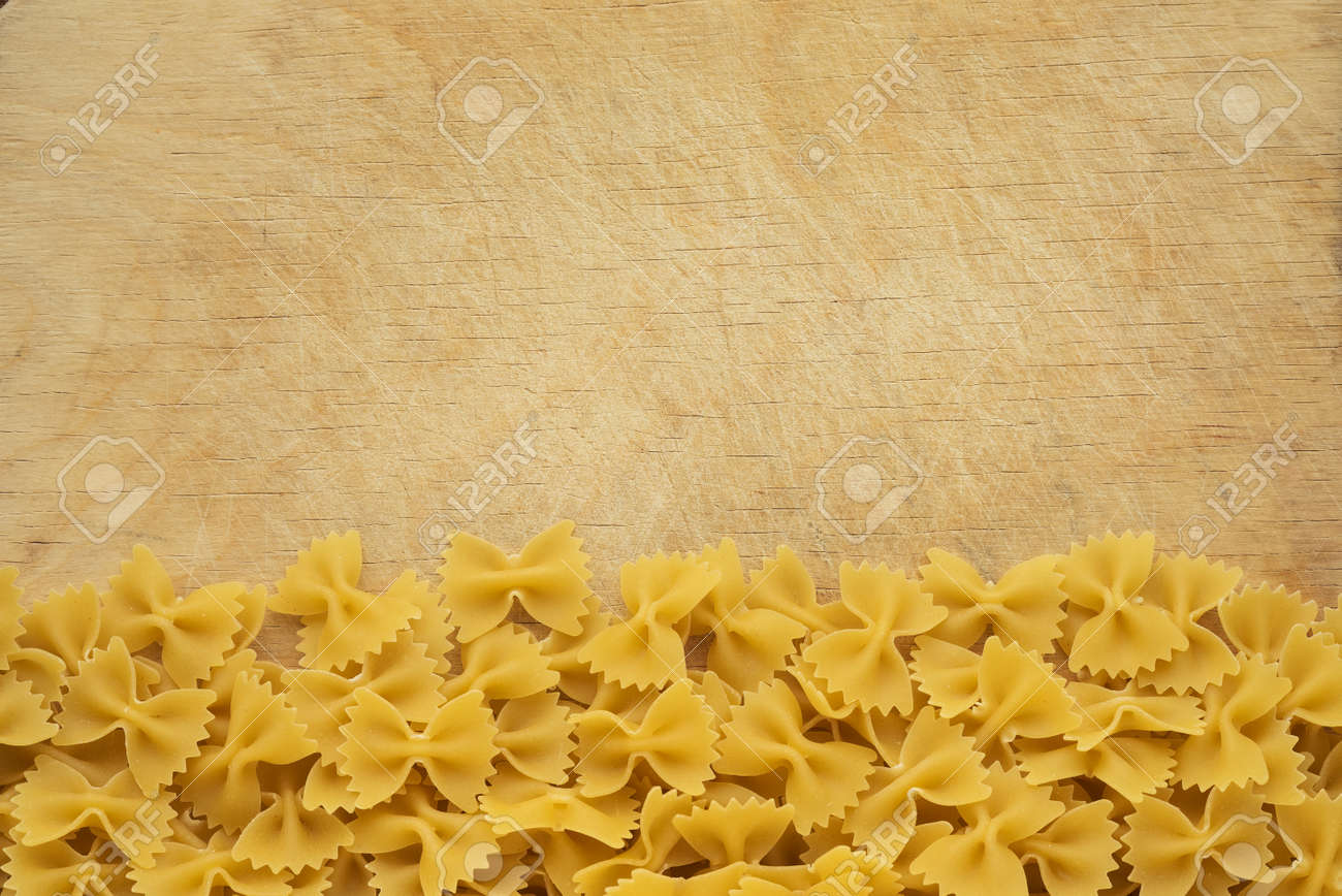 farfalle Raw farfallini Beautiful decomposed pasta with a bottom on a  wooden table top with a