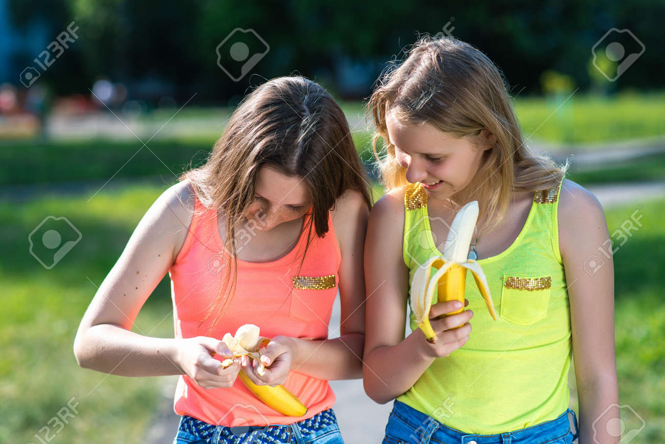 5e629c5171 Stock Photo - Two girl friends. Summer in nature. In the hands of holding  Bananas. The gestures of the hands clean the banana.