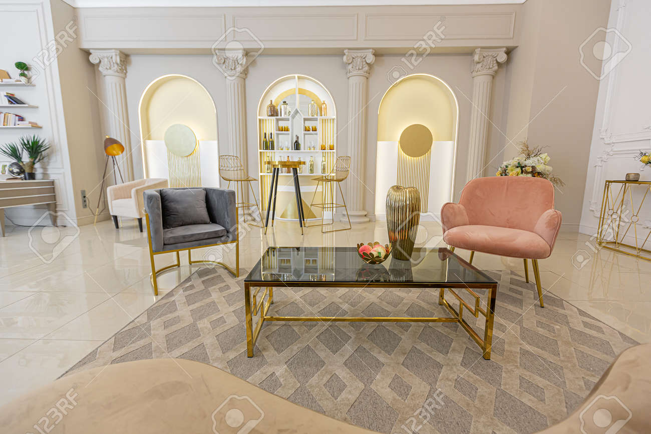 chic luxury interior in an old antique style open-plan apartment decorated with columns and stucco on the wall in pastel colors. tiles on the floor. beige walls - 156165683