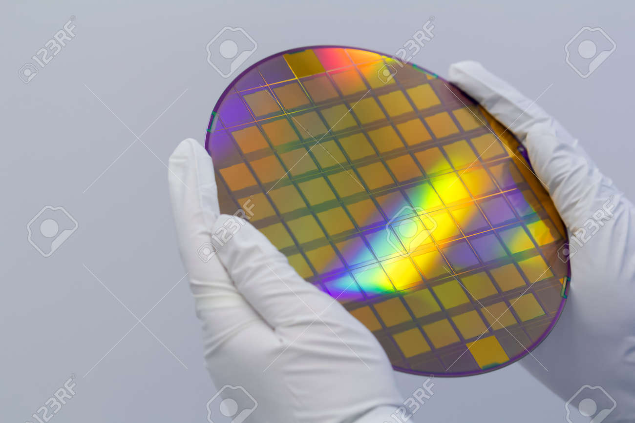 Hands in white gloves holding a silicon wafer with integrated circuits on a white background. - 146284624