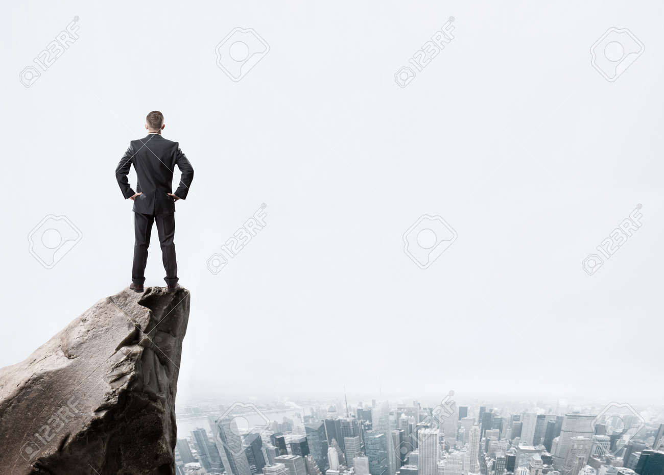Young businessman standing on edge of rock mountain and looking at the city - 41330275