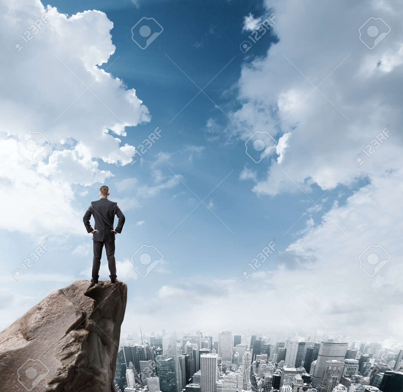Young businessman standing on edge of rock mountain and looking at the city - 41330543