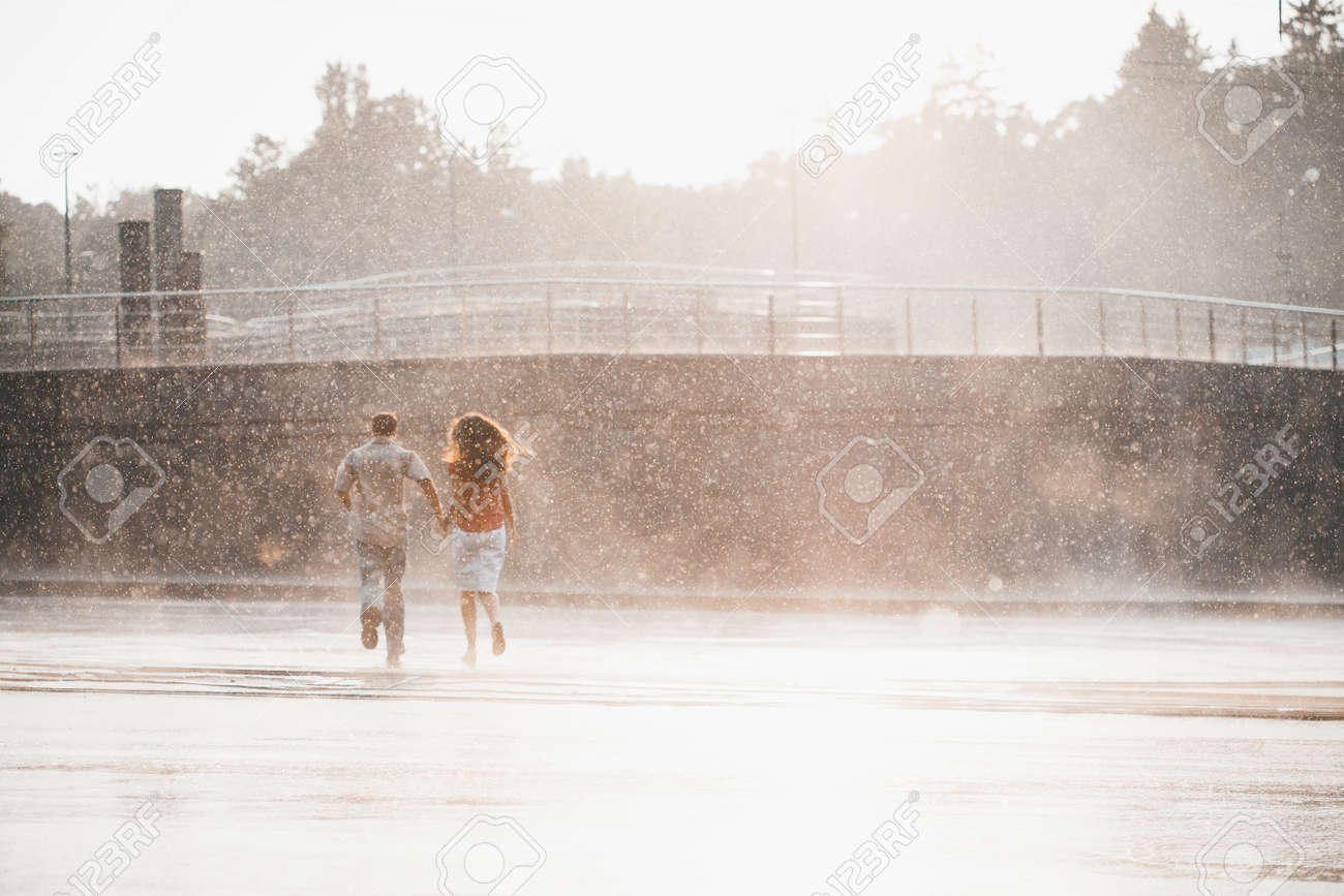 The girl with the boy run under a downpour rain - 41413331