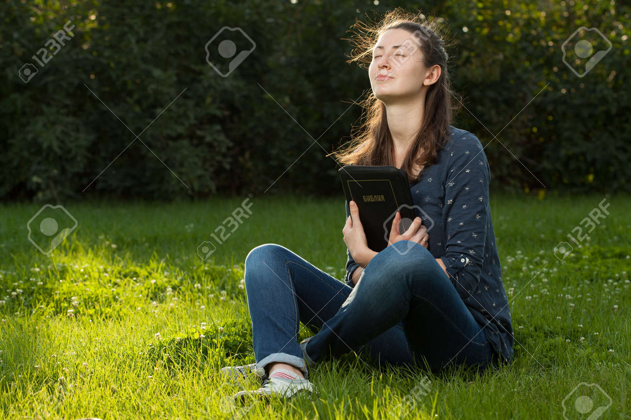 Teen girl gugging the Bible sitting outdoors with copy space - 41413983