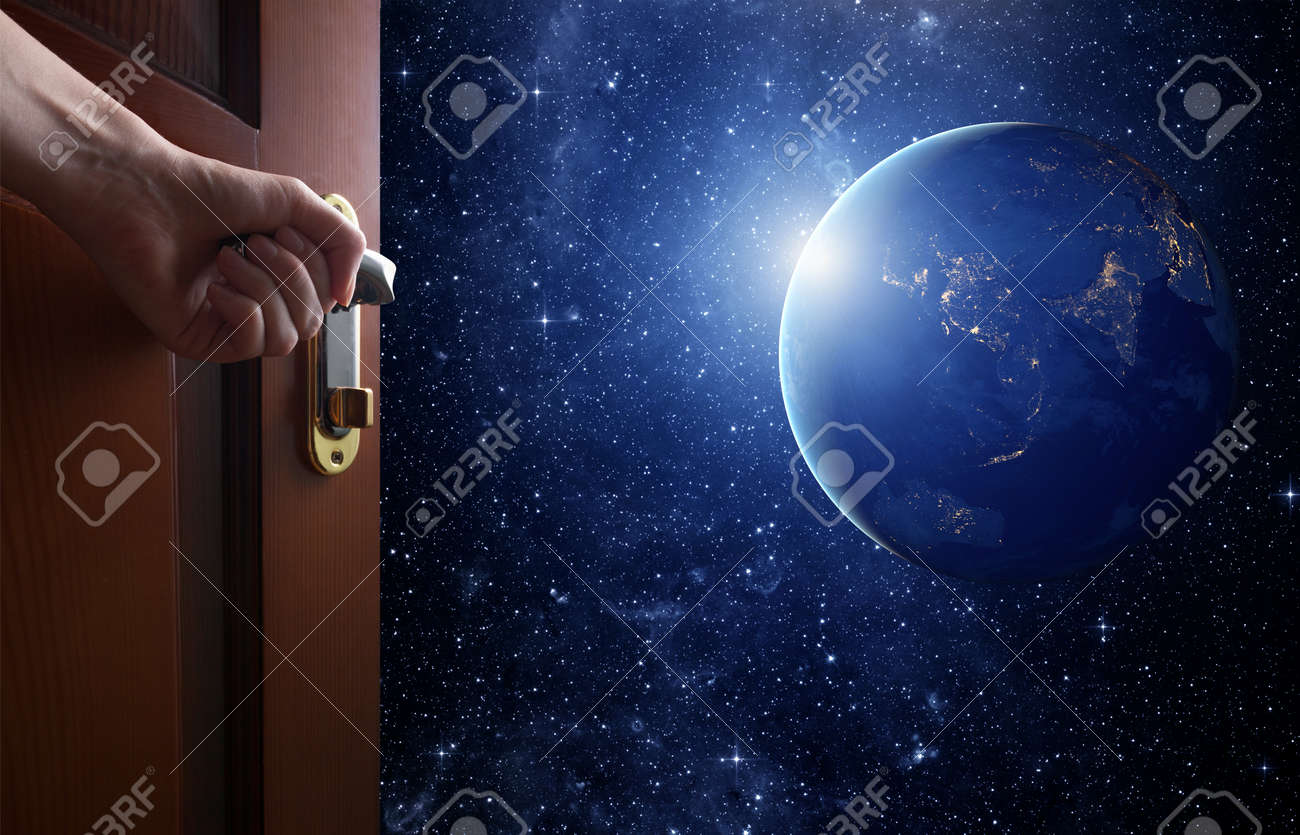 hand opens empty room door to Planet earth from the space. - 43457956