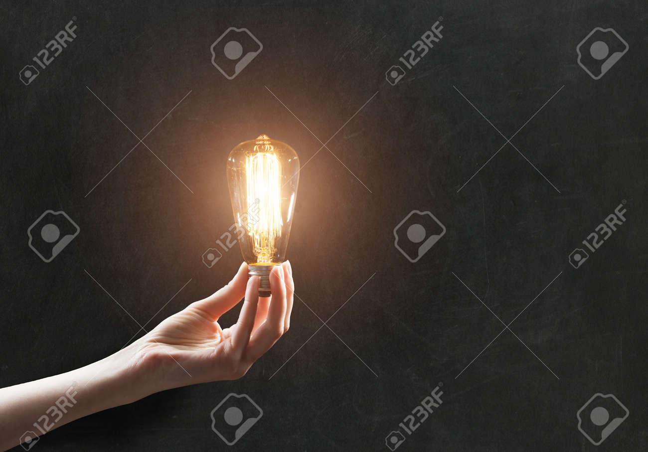 hand holding Light bulb on blackboard background - 47455934