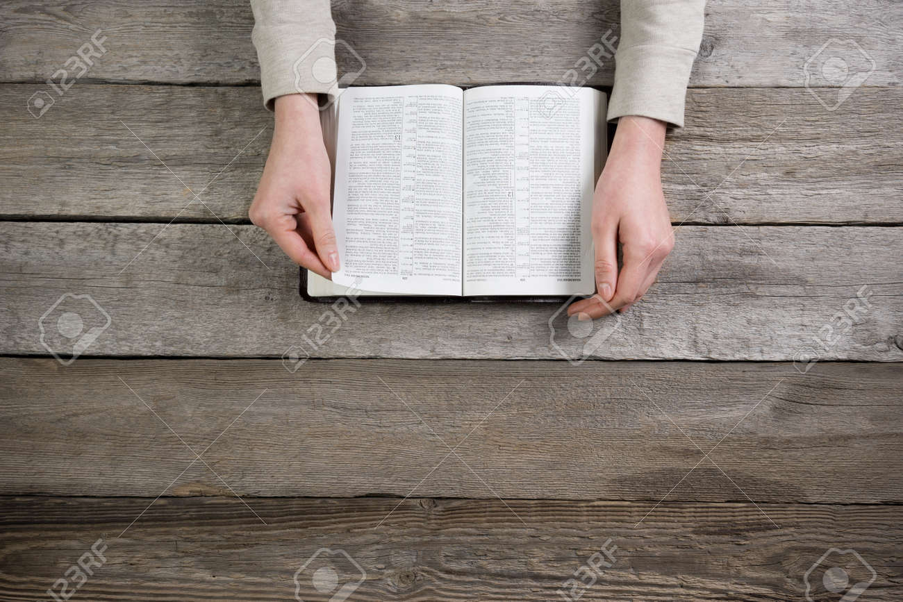 woman hands on bible. she is reading and praying over bible over wooden table - 50879139