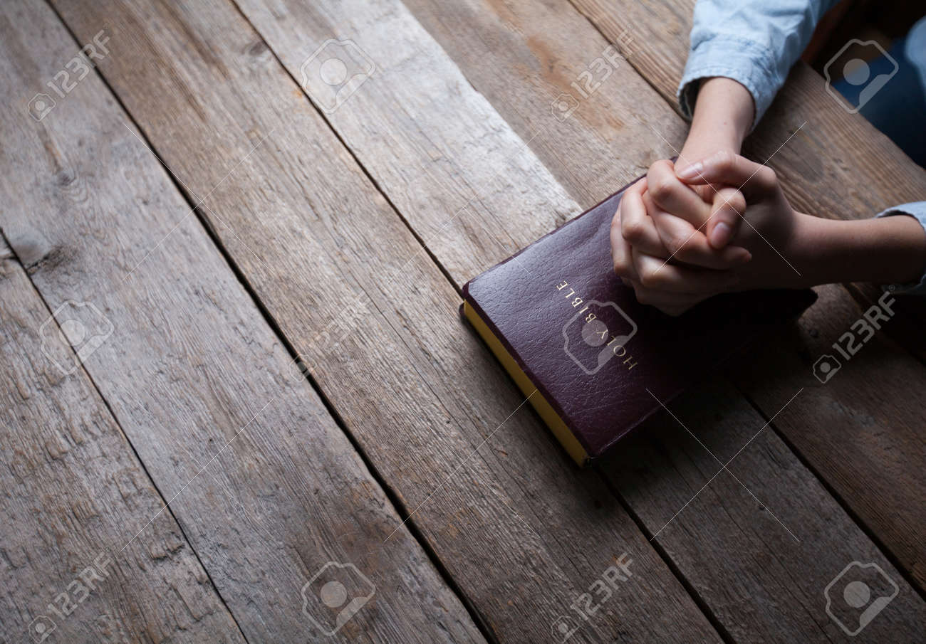 hands praying with a bible in a dark over wooden table - 54964153