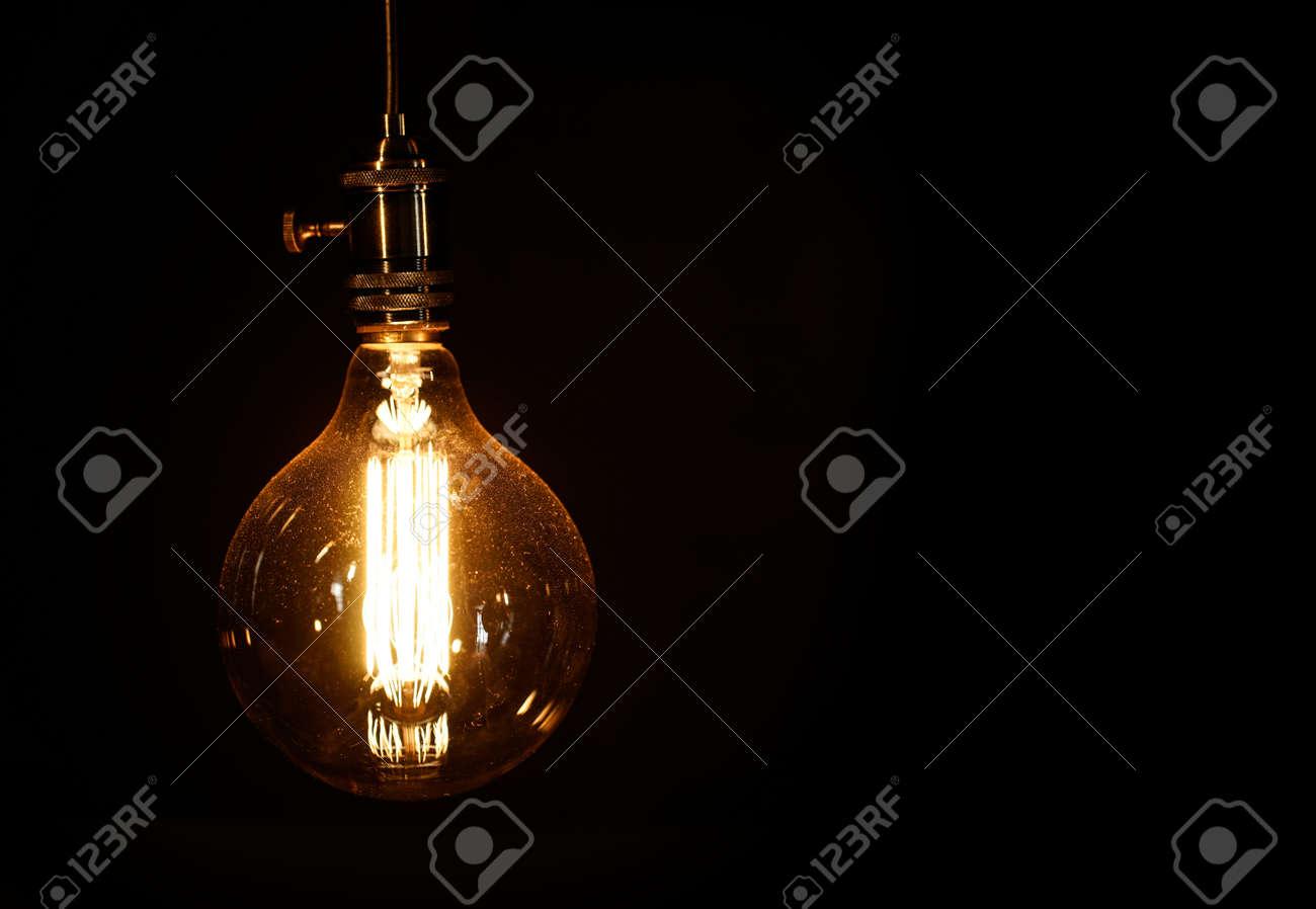 Edison light bulb on black background - 55338729