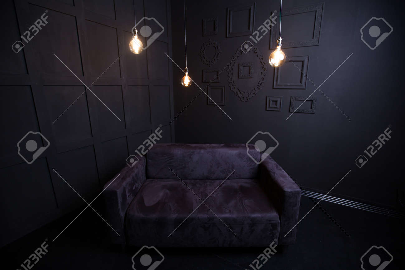 Dark room with light bulb - Black Sofa In A Dark Room With Light Bulb Stock Photo 55637647