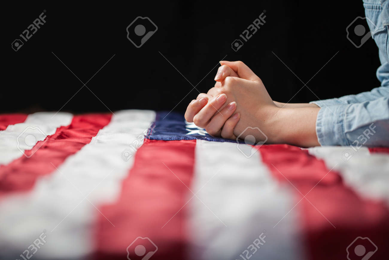 Hands praying over american flag - 57482621