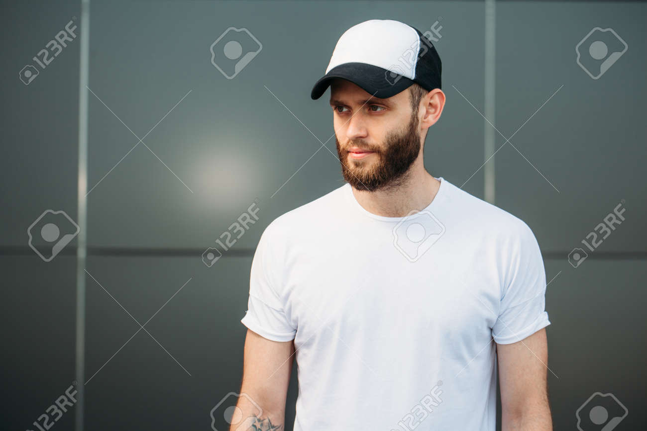 a435ed7de1182 Hipster wearing white blank t-shirt and a baseball cap with space for your  logo