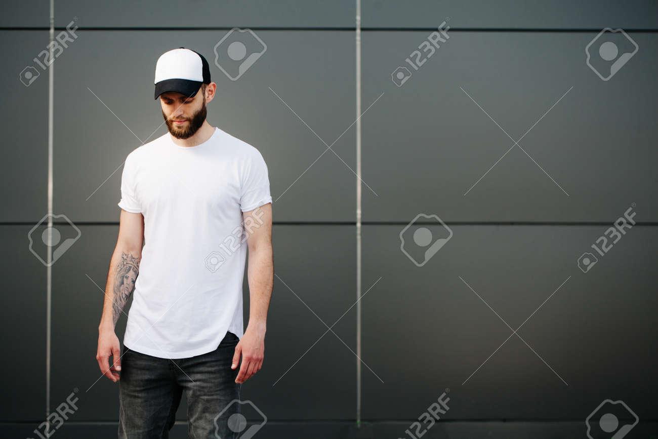 Foto de archivo - Hipster vestir de blanco en blanco camiseta y una gorra  de béisbol con el espacio para su logo 229348c172521