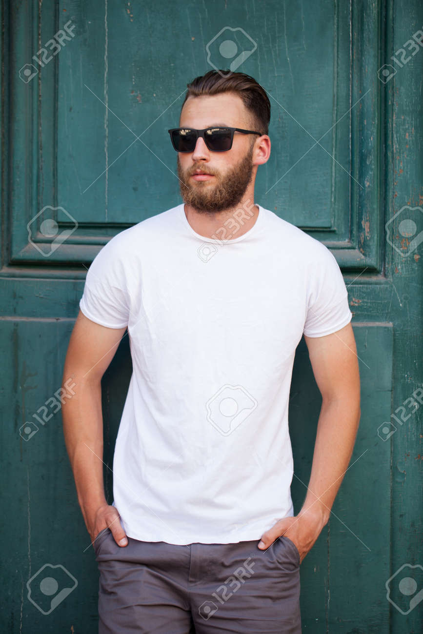 Hipster handsome male model with beard wearing white blank t-shirt with space for your logo or design in casual urban style - 82975807