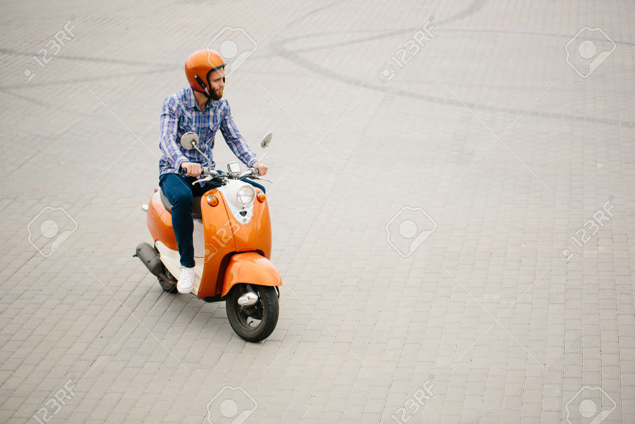 Hipster Young Man In Helmet Is Riding On Yellow Retro Scooter Stock Photo Picture And Royalty Free Image Image 85839152