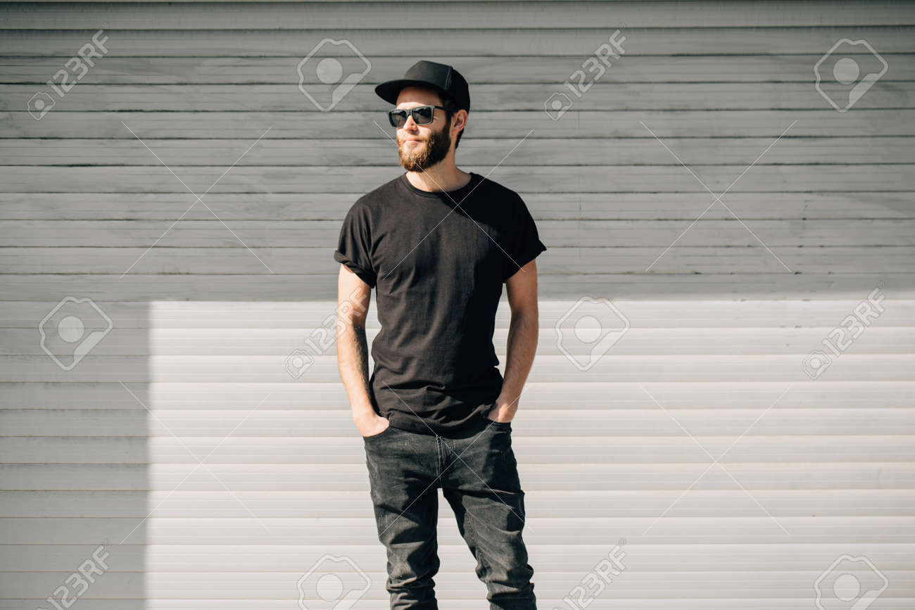 Hipster handsome male model with beard wearing black blank t-shirt with space for your logo or design in casual urban style - 87436201