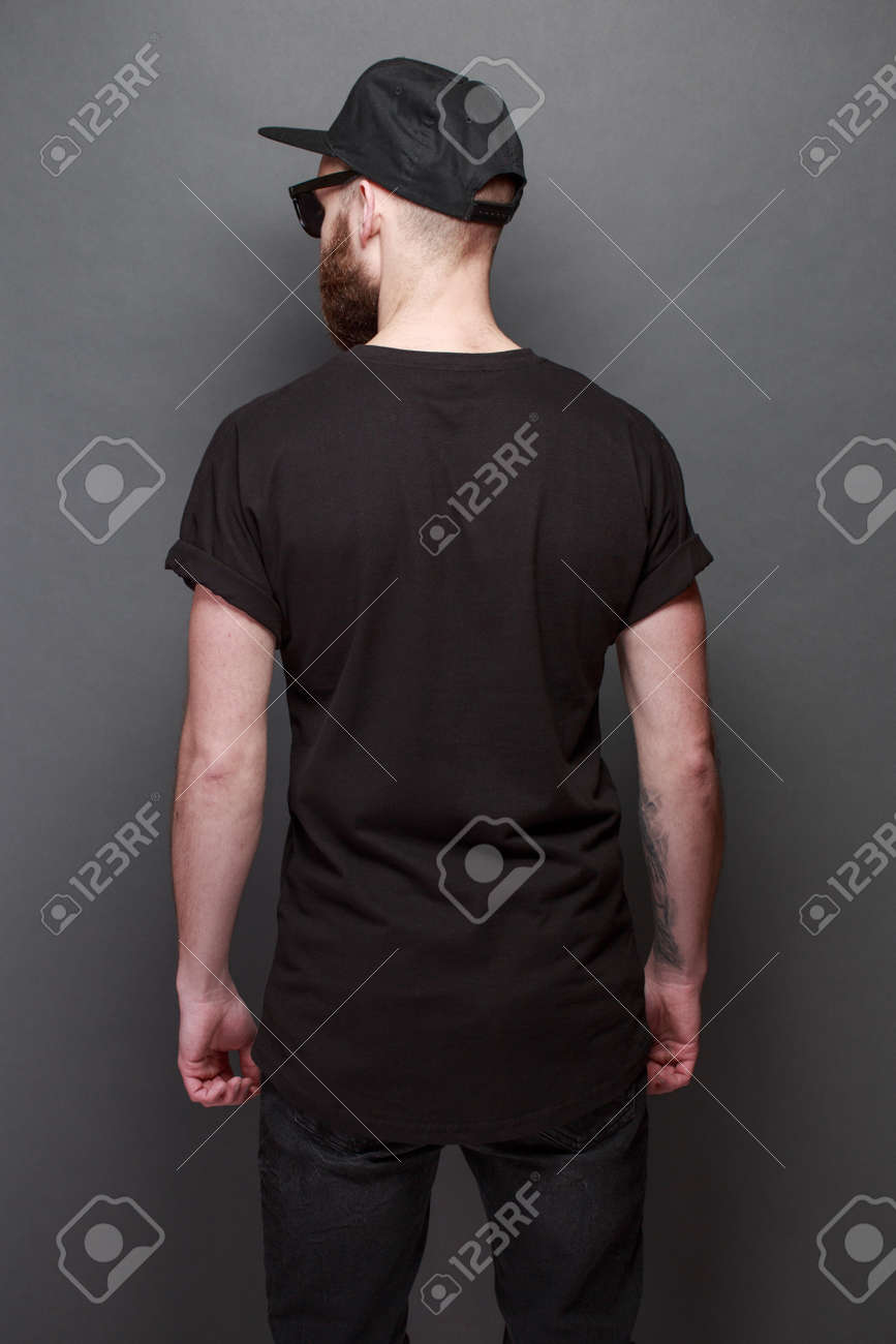 Hipster handsome male model with beard wearing black blank t-shirt with space for your logo or design over gray background - 96666673