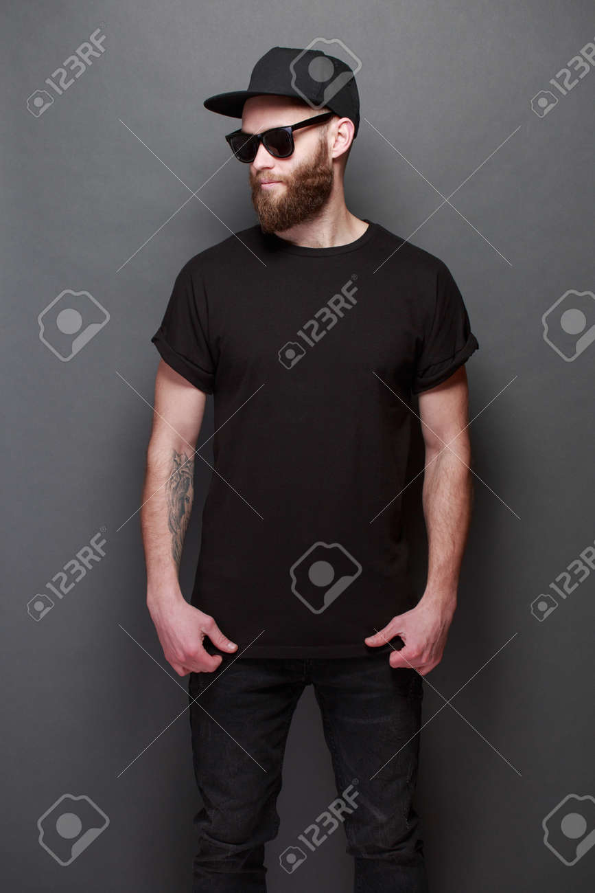 Hipster handsome male model with beard wearing black blank t-shirt with space for your design over gray background - 96828045