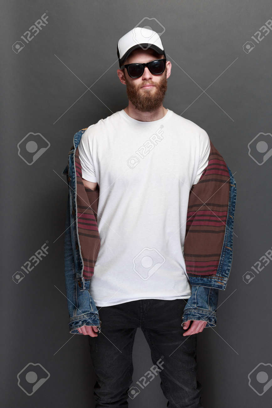 137bdf43785a9 Hipster handsome male model with beard wearing white blank t-shirt and a baseball  cap