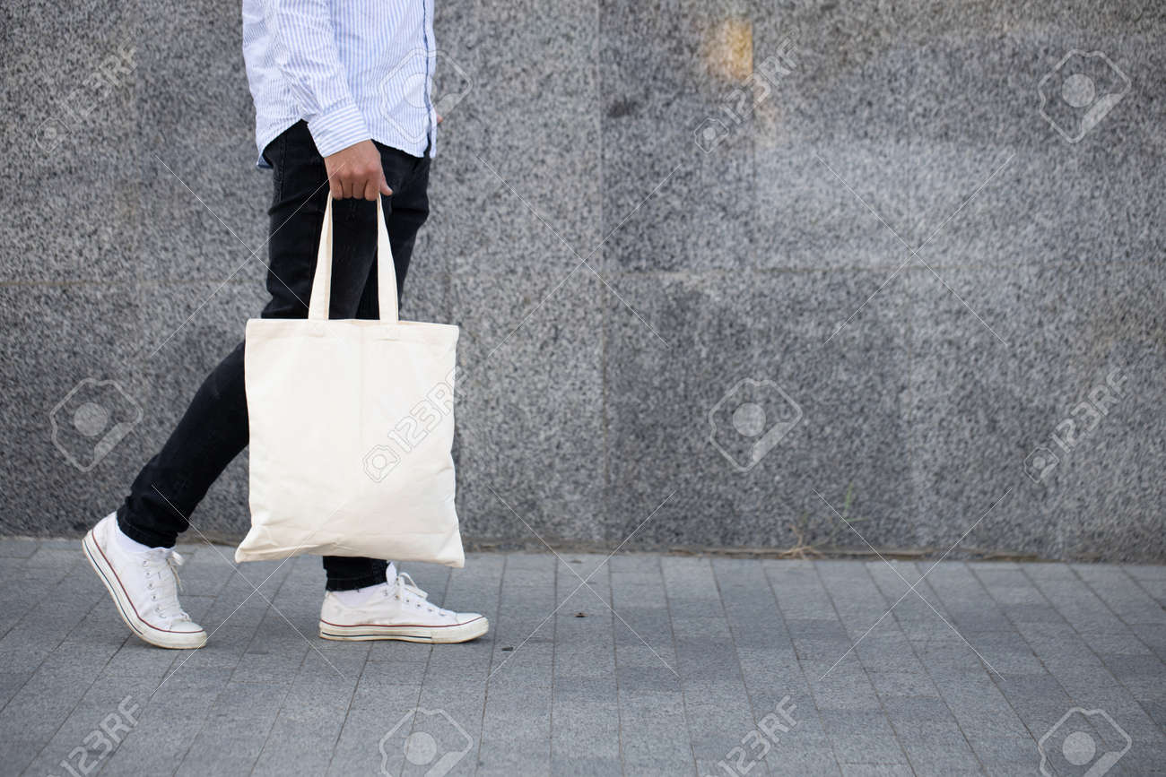 Young man holding white textile eco bag against urban city background. Ecology or environment protection concept. White eco bag for mock up. - 130533204