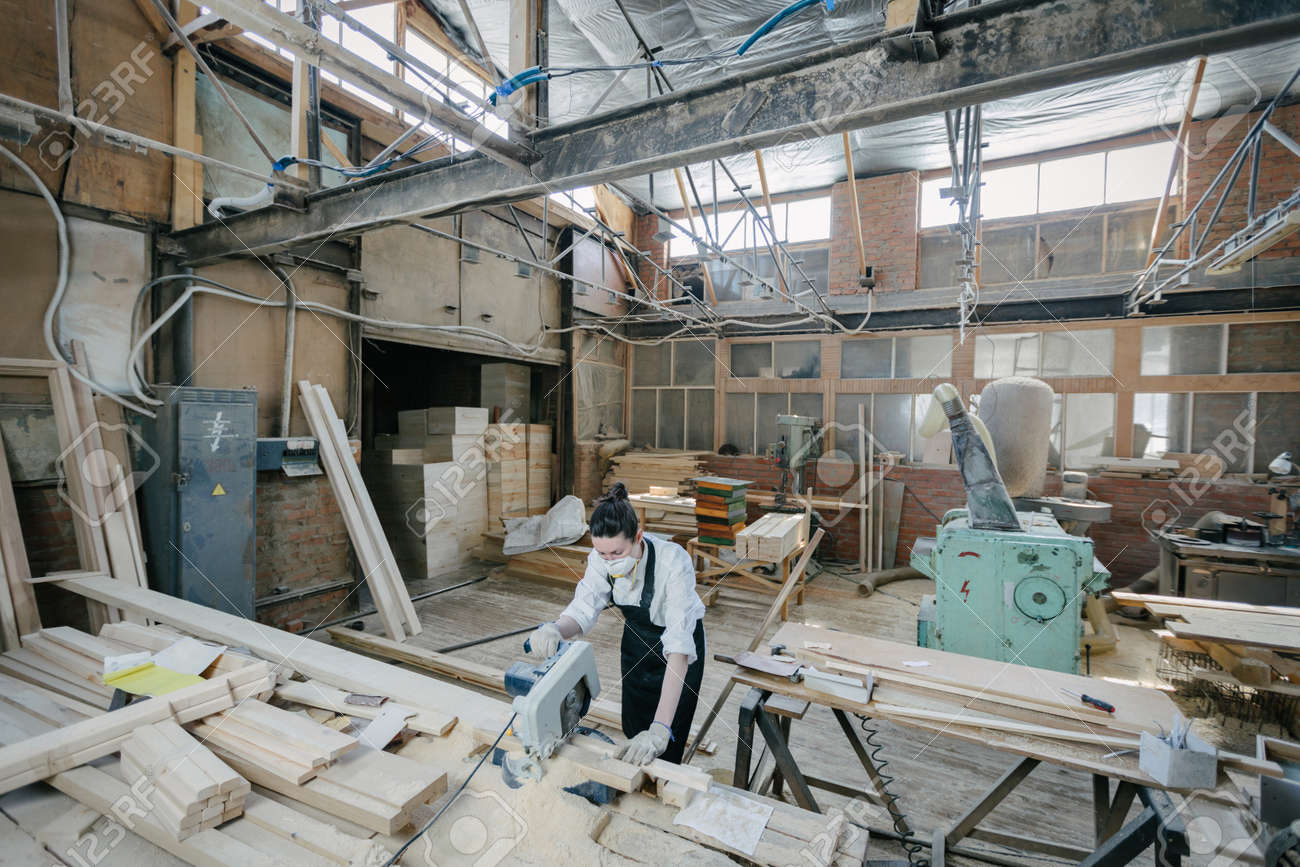 Confident woman working as carpenter in her own woodshop. Carpentry interior - 146084714