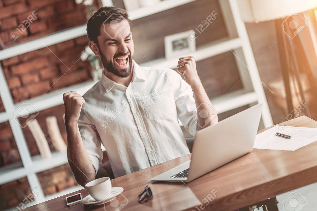 Happy handsome businessman is working with laptop in cafe. Good news. Feel of victory! - 80280517