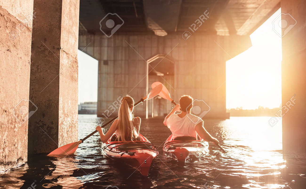 Beautiful young couple is kayaking on river. Waiting for the sunset. Canoeing together Standard-Bild - 84393318