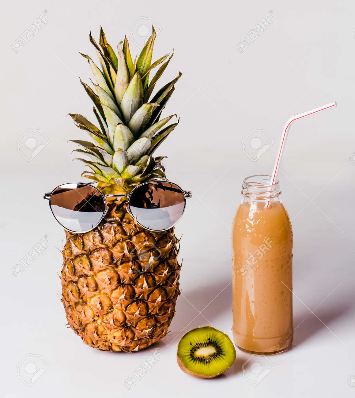 60e3b7a2c Pineapple in glasses with pineapple juice in transparent vessel and cut  kiwi on