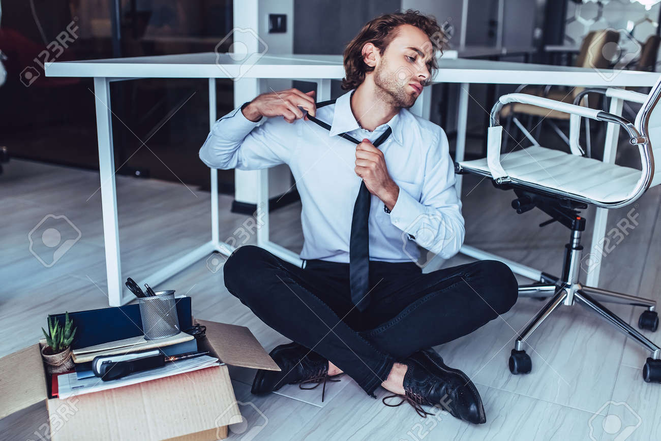 Young handsome businessman in light modern office with carton