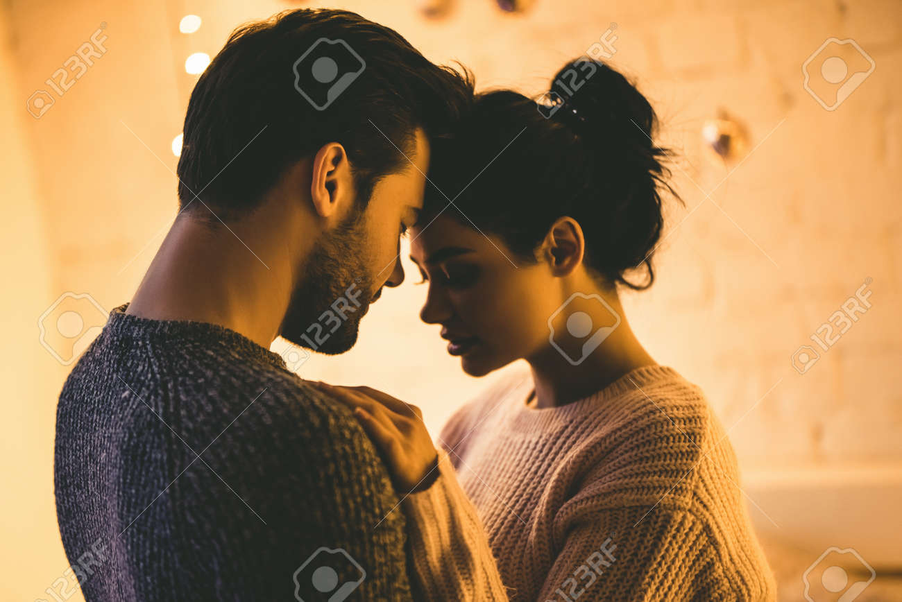 Passionate romantic couple in sweaters are spending time together before New Year at home - 90530526