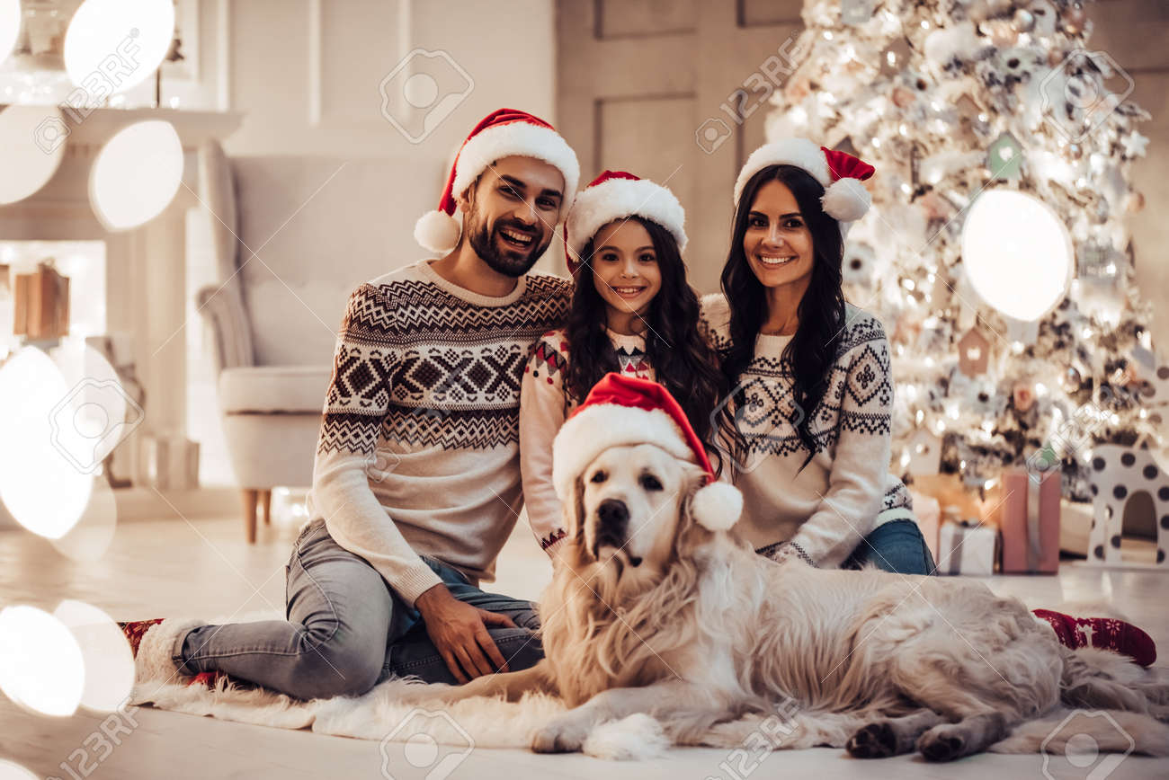 Merry Christmas and Happy New Year! Happy family with dog labrador..