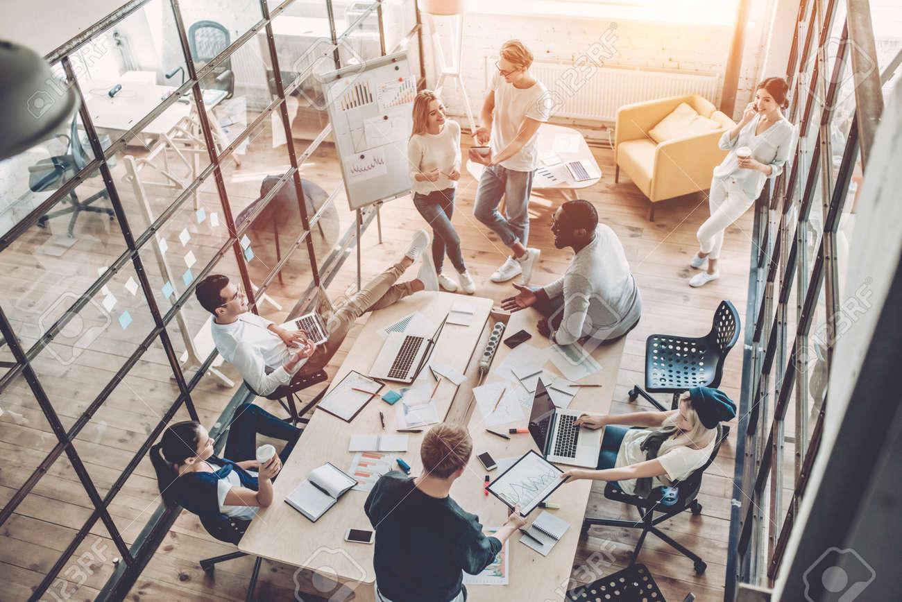 Top view of multiracial young creative people in modern office. Group of young business people are working together with laptop, tablet, smart phone, notebook. Successful hipster team in coworking. Freelancers. - 90779414