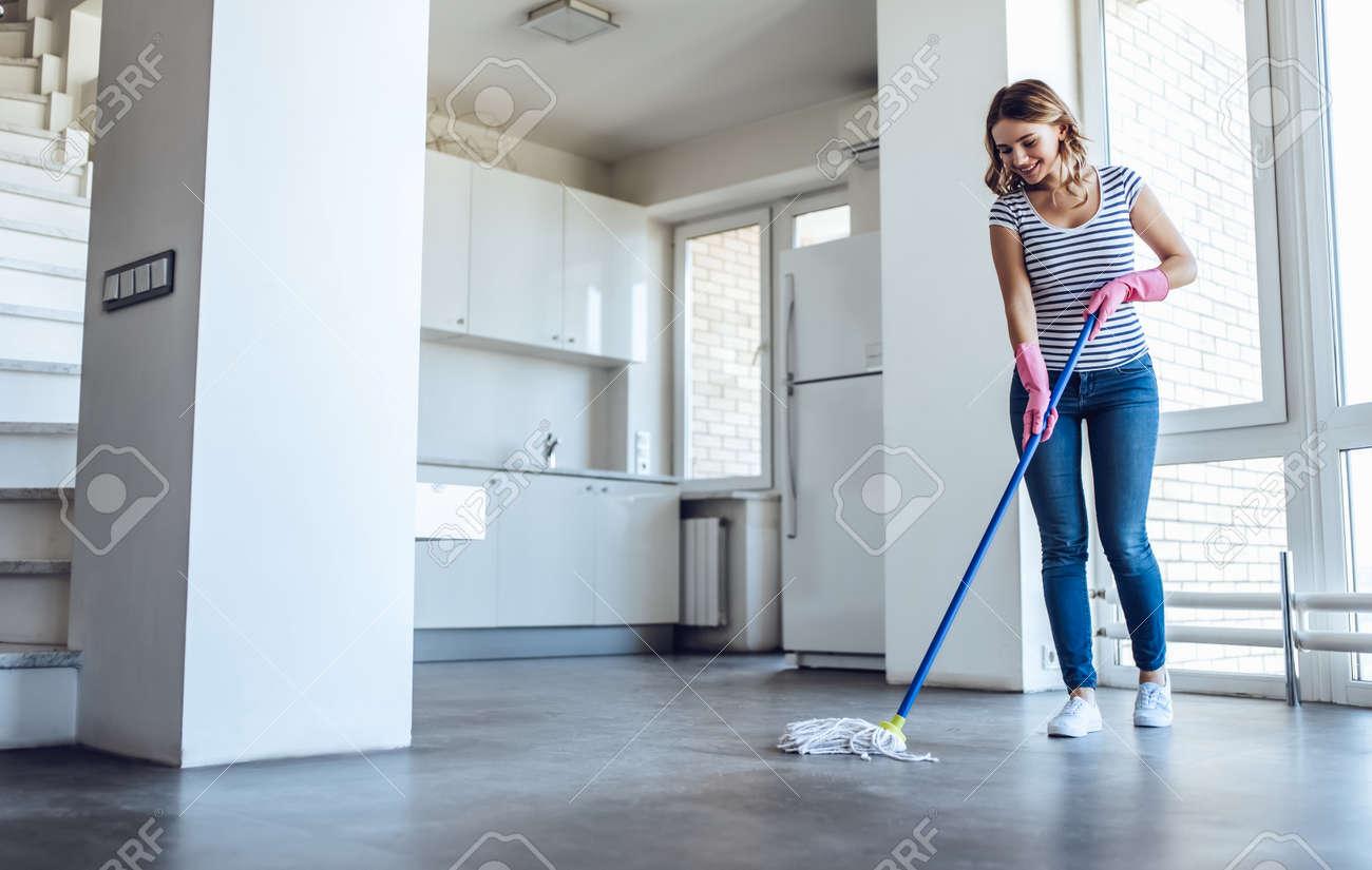 Belle jeune femme lave le sol tout en faisant le ménage à la maison
