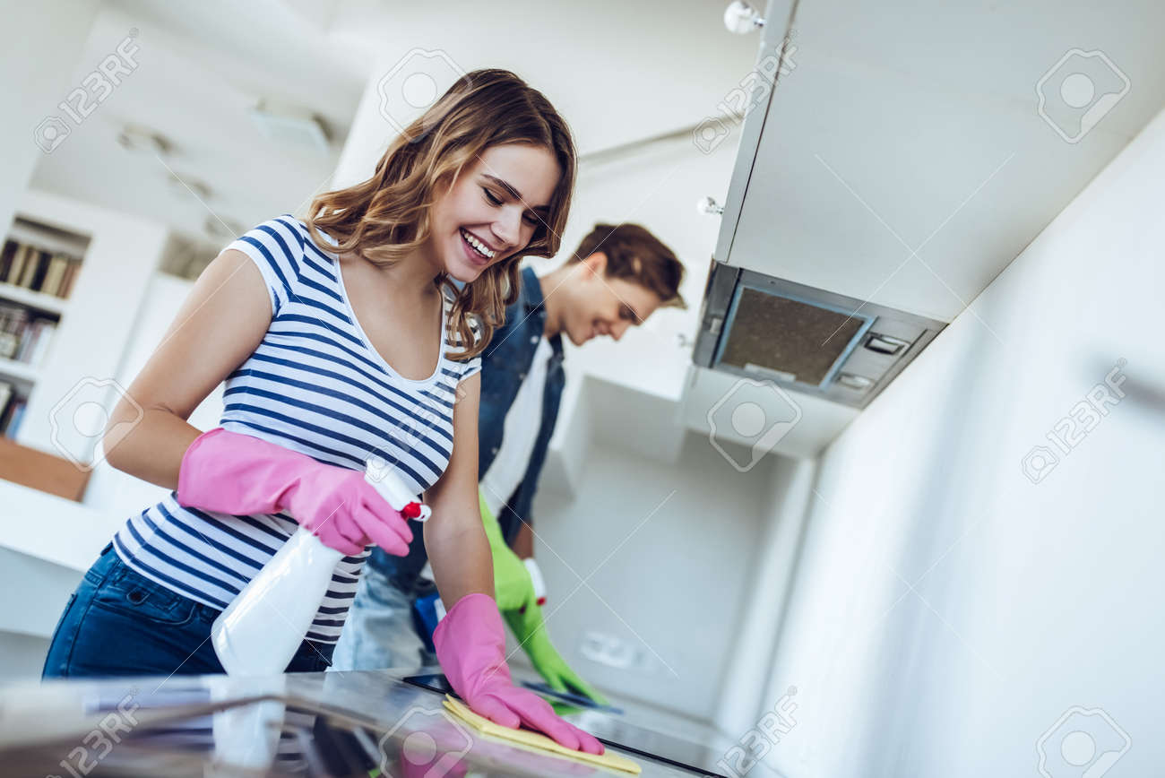 Young Happy Couple Is Washing Kitchen While Doing Cleaning At ...