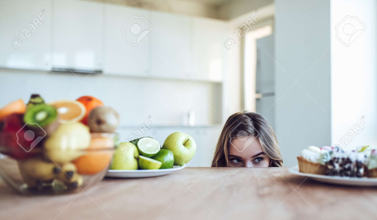 Hard choice. Yound sporty woman is choosing between fruits and sweets while standing on light kitchen. Junk food or healthy food? - 91906919