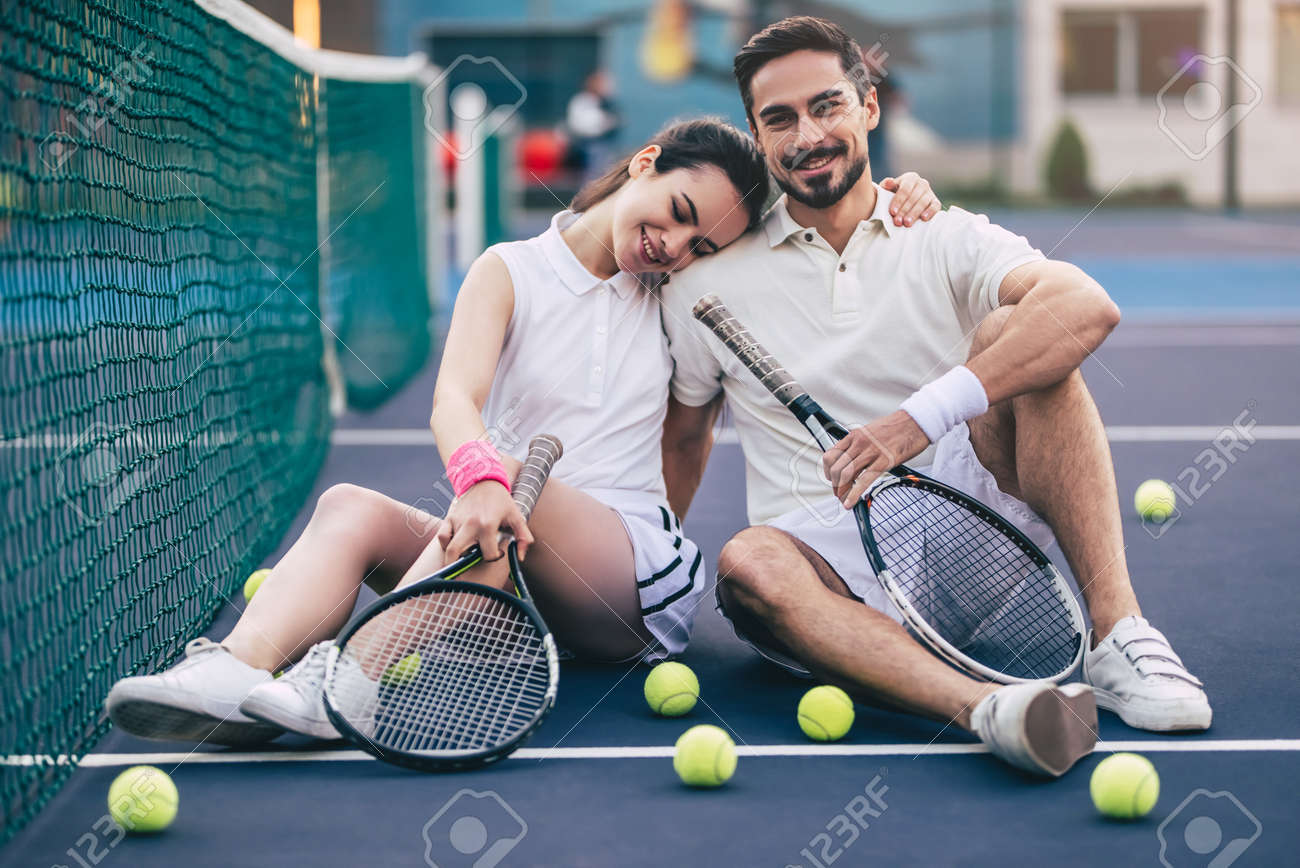Young couple is sitting on tennis court. Handsome man and attractive woman are playing tennis. - 91996713