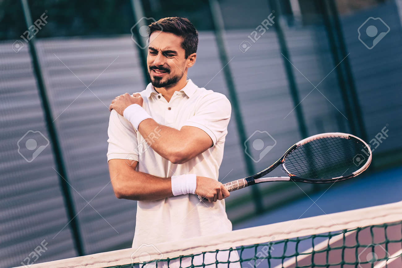 Handsome man on tennis court. Young tennis player. Shoulder pain - 92012626