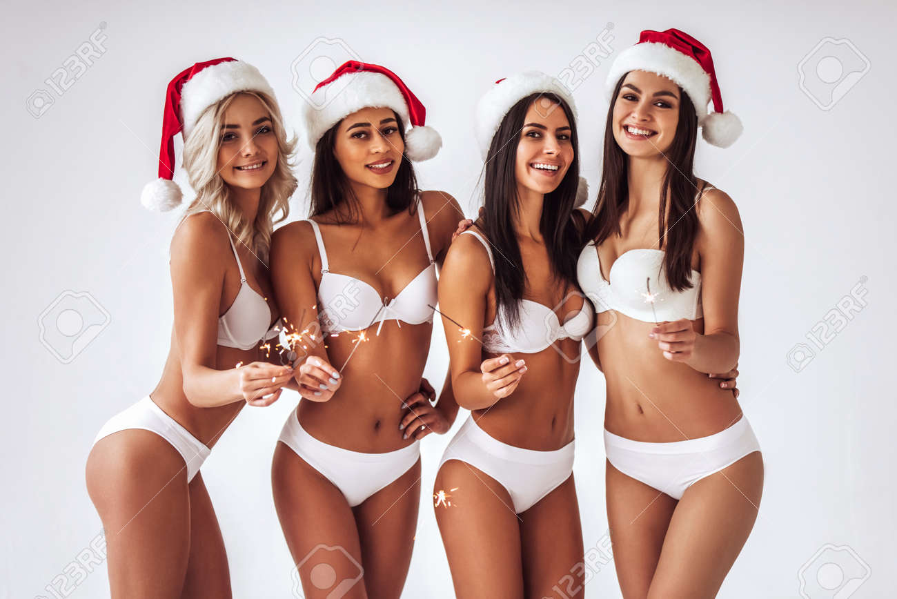 880ea2e5c Christmas and New Year celebration. Group of young sexy multiracial woman  in white lingerie are posing on white background in Santa