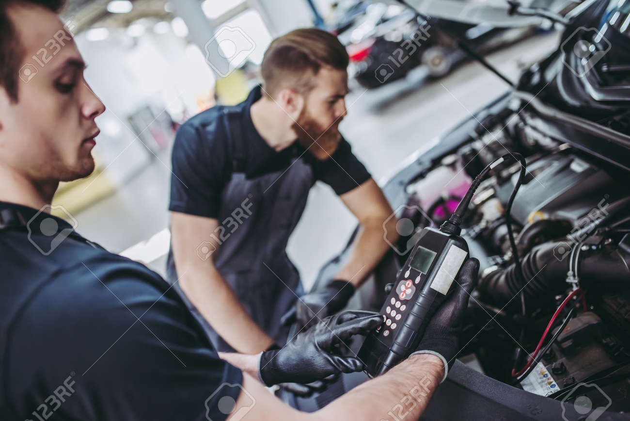 Two handsome mechanics in uniform are working in auto service. Car repair and maintenance. Performing engine diagnostics - 92240948