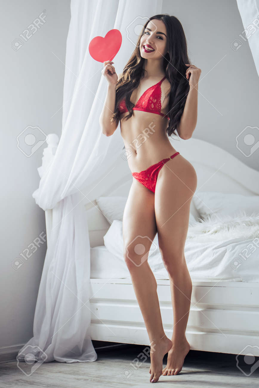 Stock Photo - Young sexy woman is standing near bed in red lingerie with  red heart in hand and smiling. Happy Saint Valentine's Day!