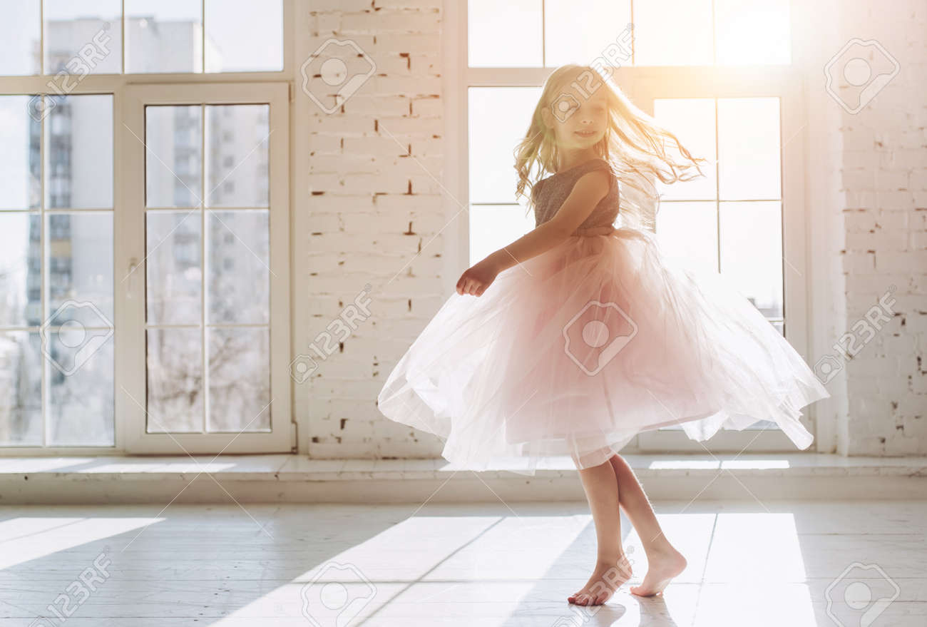Cute little girl in beautiful dress is dancing at light sunny room - 96046029