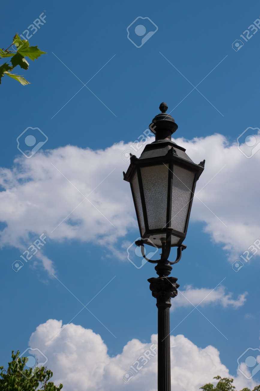 antique street light in front of cloudy sky