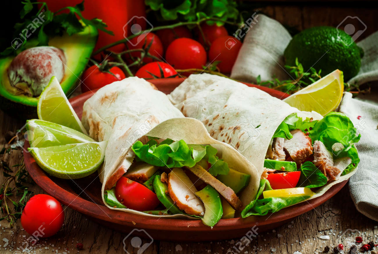 Fresh roll shawarma (doner) with meat, avocado, cherry tomatoes, peppers and lettuce on a clay plate, dark toned image, street food concept, selective focus - 151178015