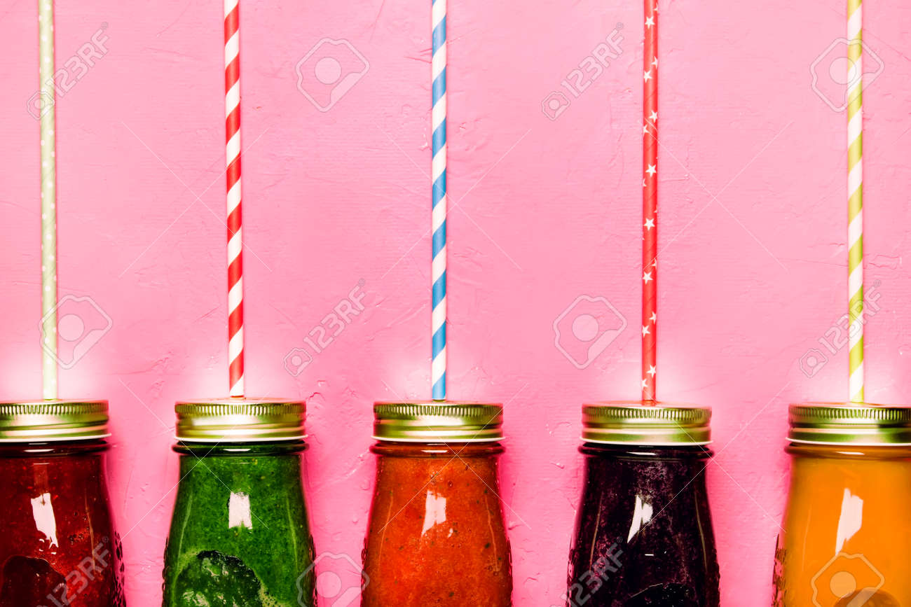 Multicolored detox vegan vegetable juices and smoothies in glass bottles on pink table, raw diet and clean food concept, drink background, copy space, top view - 151272454