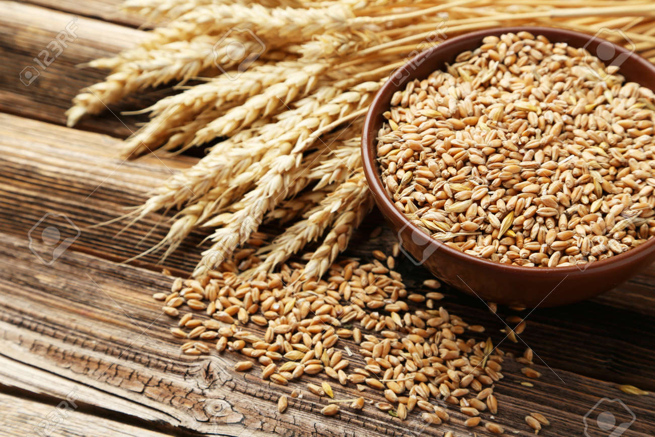 Ears of wheat and bowl of wheat grains on brown wooden background - 41910581