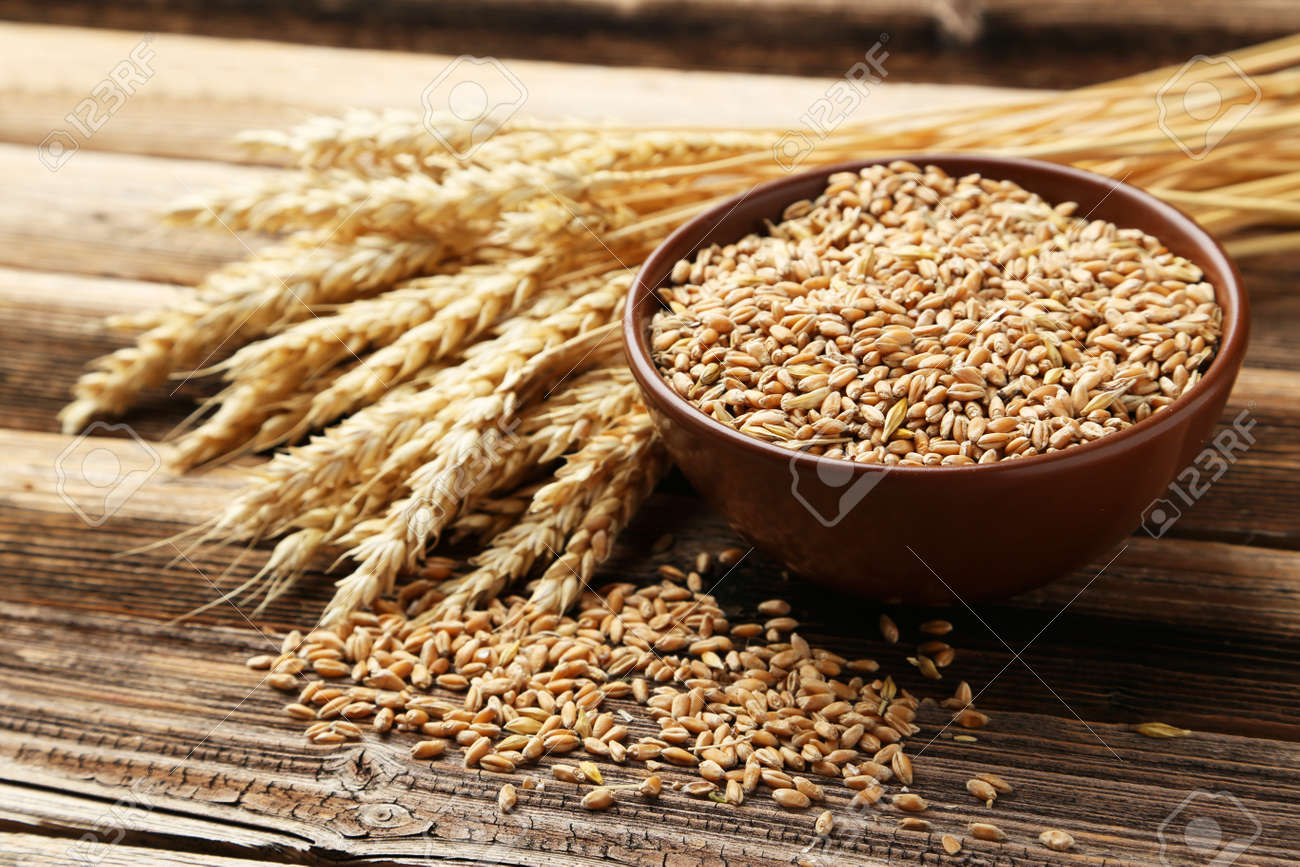 Ears of wheat and bowl of wheat grains on brown wooden background - 42880181