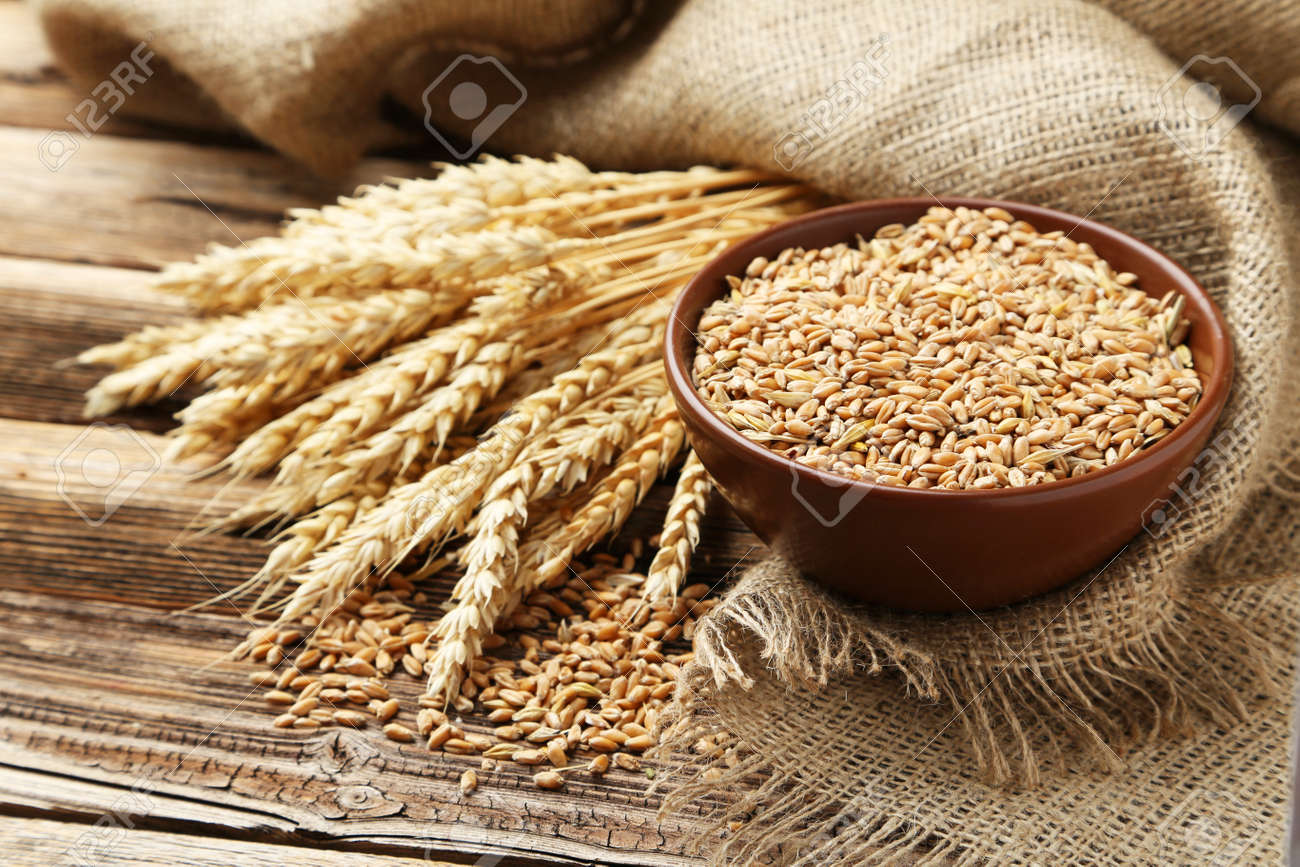 Ears of wheat and bowl of wheat grains on brown wooden background - 42880146